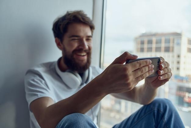 Homem barbudo sentado no parapeito da janela em fones de ouvido com tecnologia de fones de ouvido