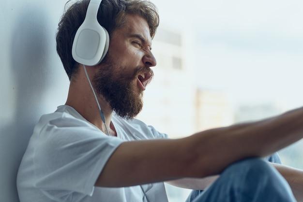 Homem barbudo sentado no peitoril da janela tecnologias