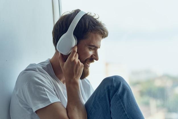 Homem barbudo sentado perto da janela com fones de ouvido ouvindo música