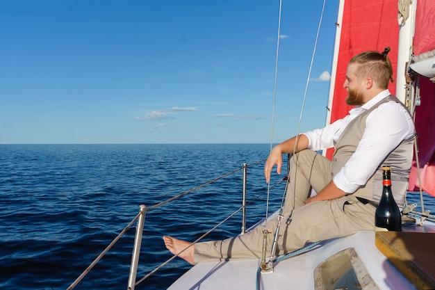 Homem barbudo sentado relaxado ao lado do mastro com uma garrafa de espumante em um veleiro