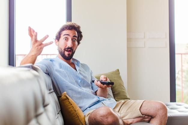Homem barbudo sentindo-se extremamente chocado e surpreso, ansioso e em pânico, com um olhar estressado e horrorizado