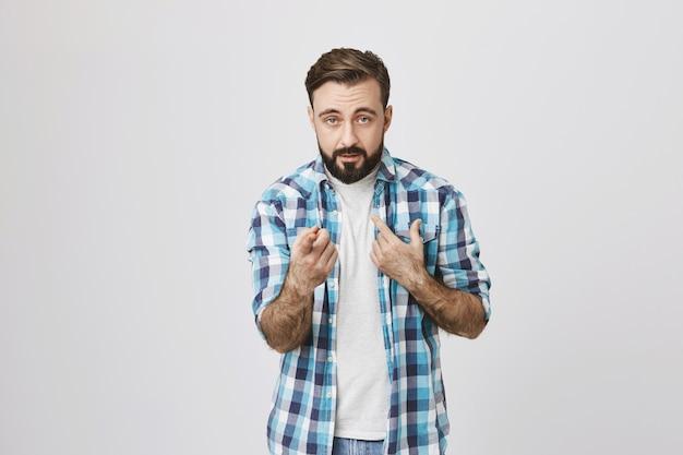 Homem barbudo sério apontando para si mesmo e para você
