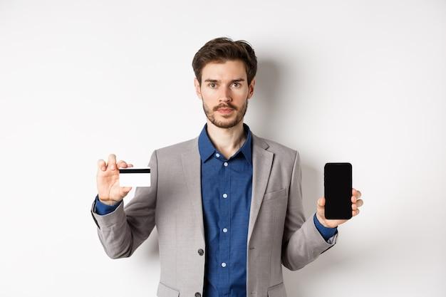 Homem barbudo sério em um terno de negócio, mostrando um cartão de crédito de plástico com a tela do smartphone vazia