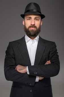 Homem barbudo sério em um terno e um chapéu.