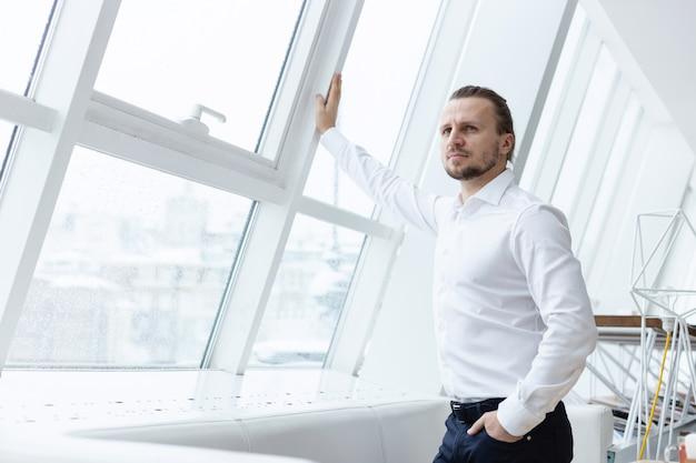 Homem barbudo sério inclinou-se em uma janela por suas mãos em pé no interior moderno