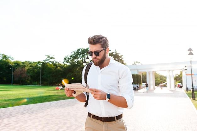 Homem barbudo sério lendo jornal ao ar livre