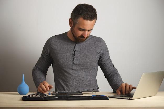 Homem barbudo sério olhando para o telefone desmontado e trabalhando no laptop para pedir as peças necessárias para trocá-lo