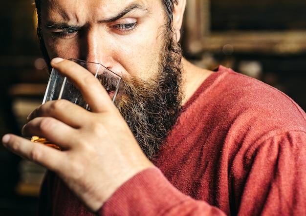 Homem barbudo sério prova bebida alcoólica.