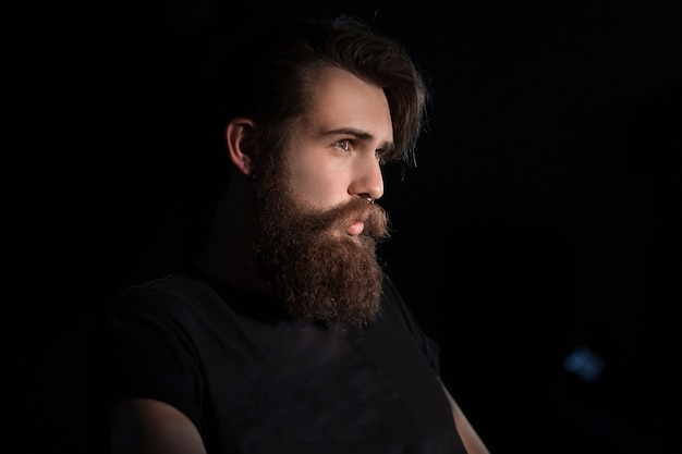 Homem barbudo sério sentado em uma cadeira