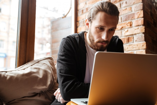 Homem barbudo sério usando laptop no café