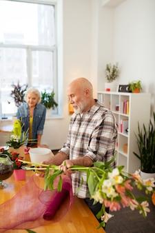 Homem barbudo simpático segurando flores nas mãos enquanto as usa para criar um buquê