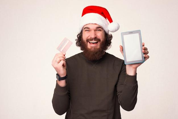 Homem barbudo sorridente com chapéu de natal está segurando o cartão do banco e o tablet dele.