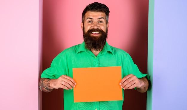 Homem barbudo sorridente com pequena placa de publicidade. banner de publicidade com espaço de cópia para texto.