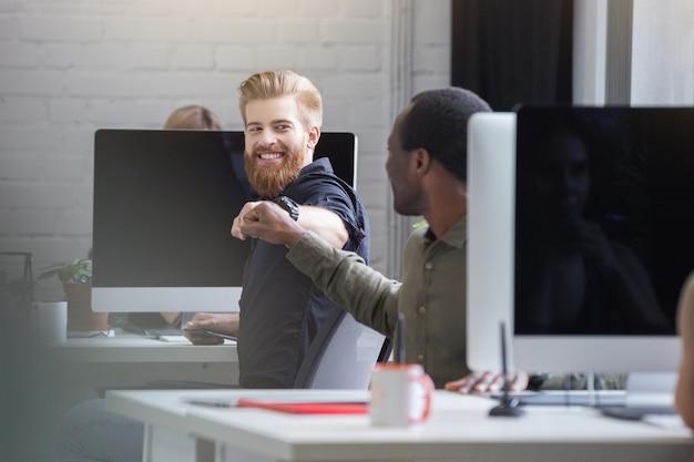 Homem barbudo sorridente, dando uma colisão do punho para um colega do sexo masculino