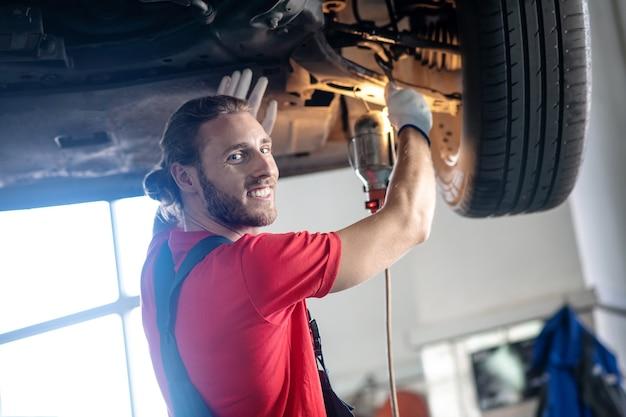 Homem barbudo sorridente e alegre de macacão consertando carro em oficina mecânica à tarde