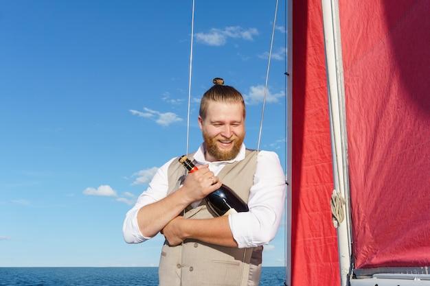 Homem barbudo sorridente em um colete com uma garrafa de espumante ao lado do mastro em um veleiro