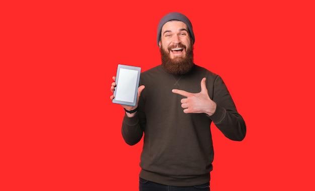 Homem barbudo sorridente está apontando para o tablet que ele está segurando.