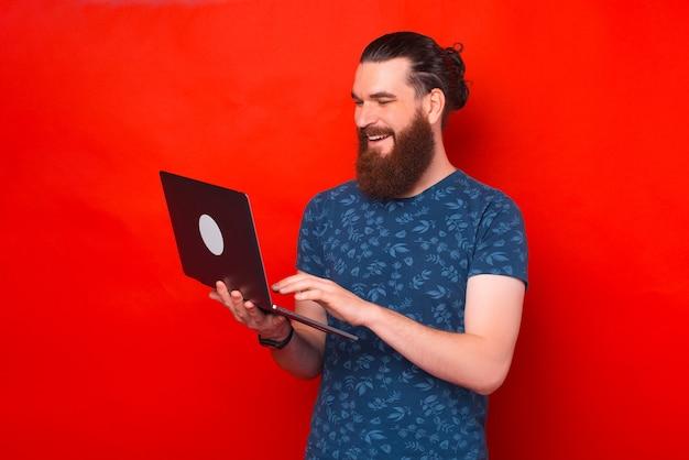 Homem barbudo sorridente está segurando seu laptop, digitando ou navegando.