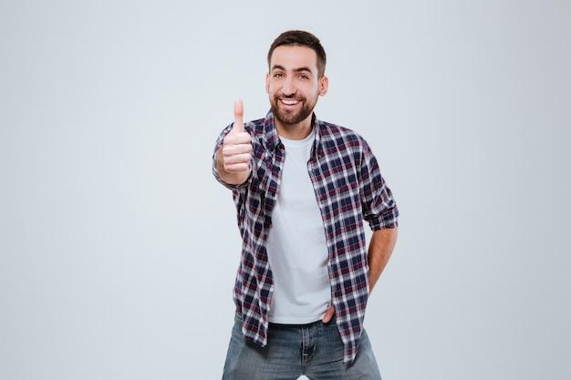 Homem barbudo sorridente na camisa aparecendo polegar em