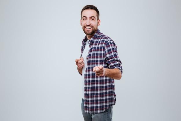 Homem barbudo sorridente na camisa, apontando para você