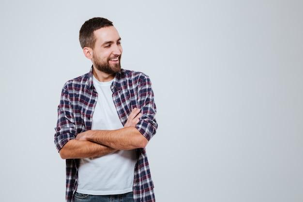 Homem barbudo sorridente na camisa com os braços cruzados