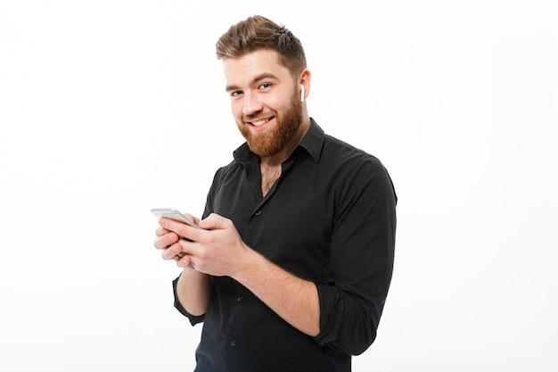 Homem barbudo sorridente na camisa segurando o smartphone