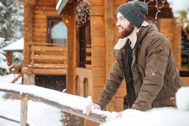 Homem barbudo sorridente no inverno usa em pé perto de uma cabana de madeira no inverno