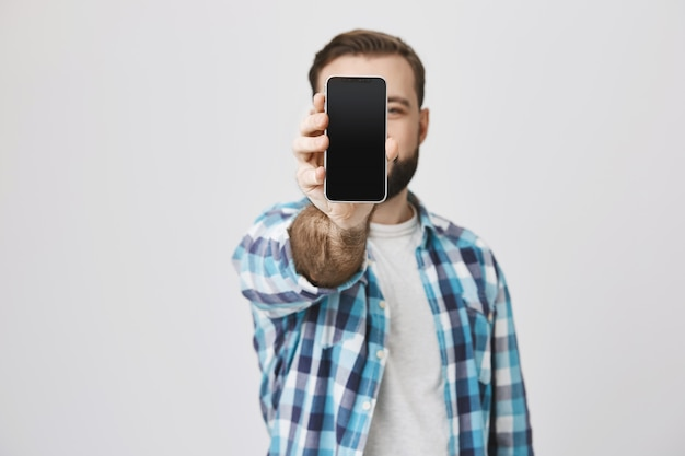 Homem barbudo sorridente satisfeito mostrando a tela do smartphone, promoção de aplicativo