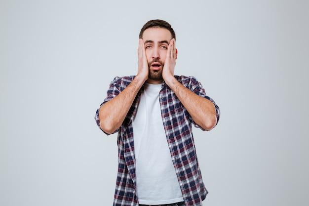 Homem barbudo surpreso na camisa segurando suas bochechas