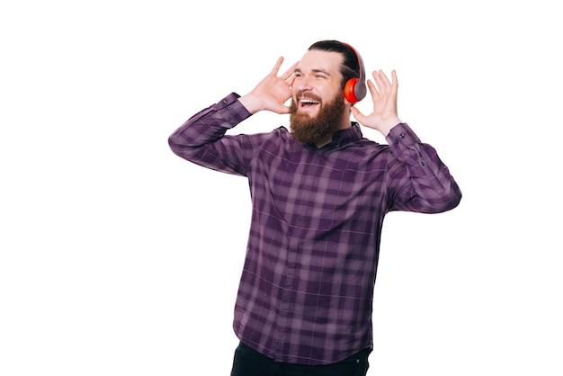 Homem barbudo surpreso ouvindo música em fones de ouvido vermelhos