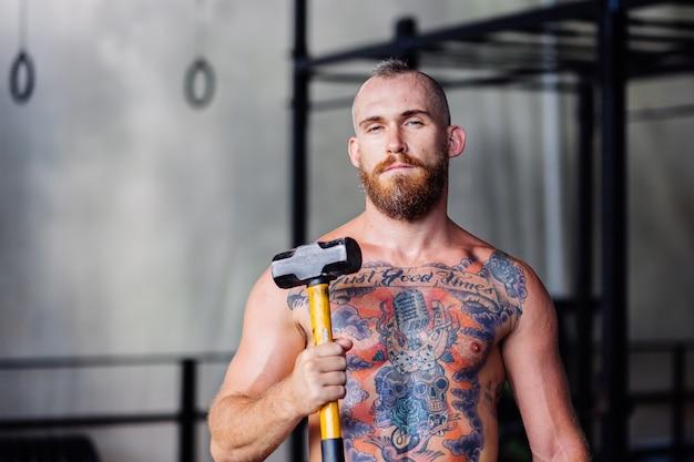 Homem barbudo tatuado e bonito na academia com um martelo