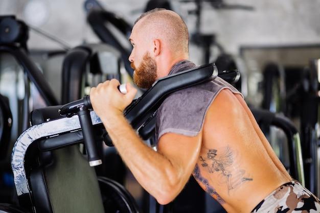 Homem barbudo tatuado fazendo agachamentos em uma máquina de treinamento