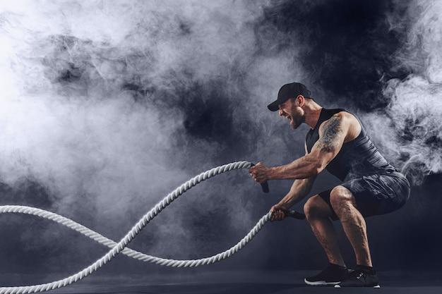 Homem barbudo tatuado musculoso se exercitando