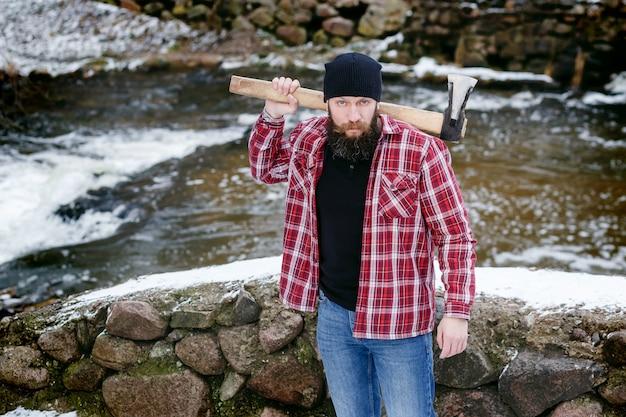 Homem barbudo tem nas mãos um machado na floresta de inverno