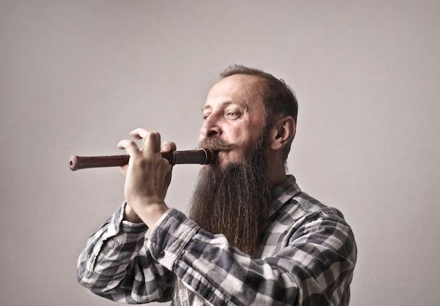 Homem barbudo tocando uma flauta