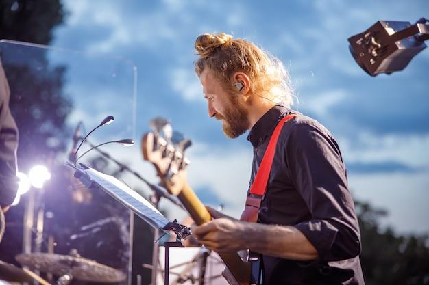 Homem barbudo tocando violão em show ao ar livre
