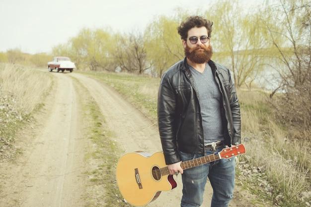 Homem barbudo tocando violão, perto de carro retrô