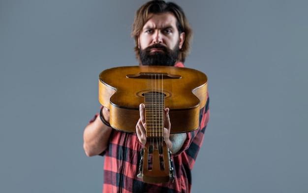 Homem barbudo tocando violão, segurando um violão nas mãos.