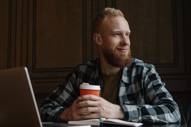 Homem barbudo tomando café no café