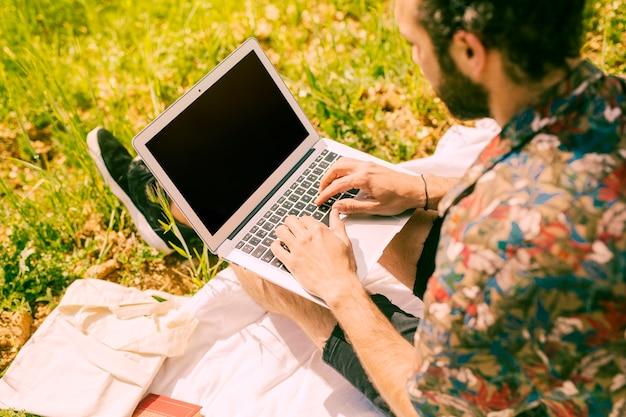 Homem barbudo trabalhando no laptop no prado