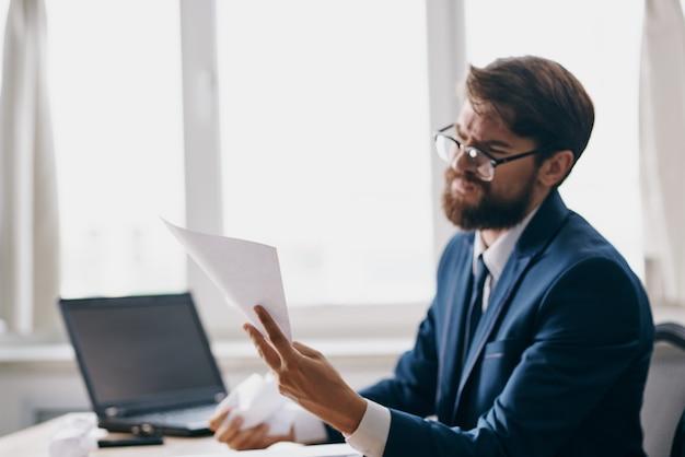 Homem barbudo trabalhando para um laptop no escritório emoções descontentamento profissional