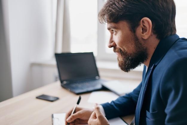 Homem barbudo trabalhando para um laptop no escritório profissional de emoções