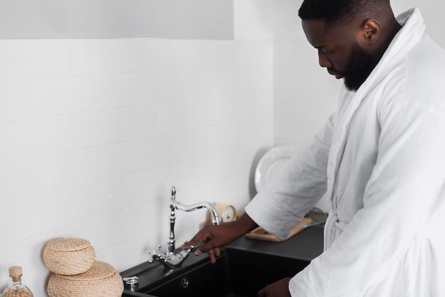 Homem barbudo, transformando a água da torneira