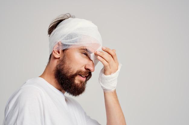 Homem barbudo traumatismo cranioencefálico em camiseta branca dor de cabeça remédio hospitalar