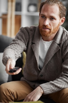 Homem barbudo, trocando de canal de tv