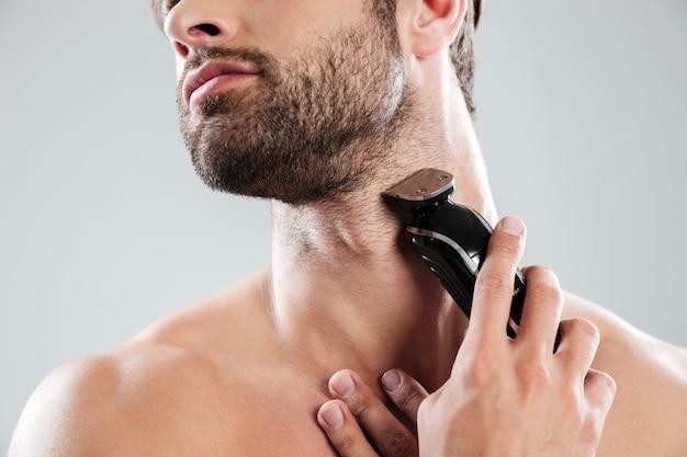 Homem barbudo usando barbeador elétrico