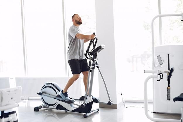 Homem barbudo usando bicicleta de spinning na sala de fisioterapia
