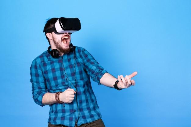 Homem barbudo usando óculos de realidade virtual, brincando emocionalmente