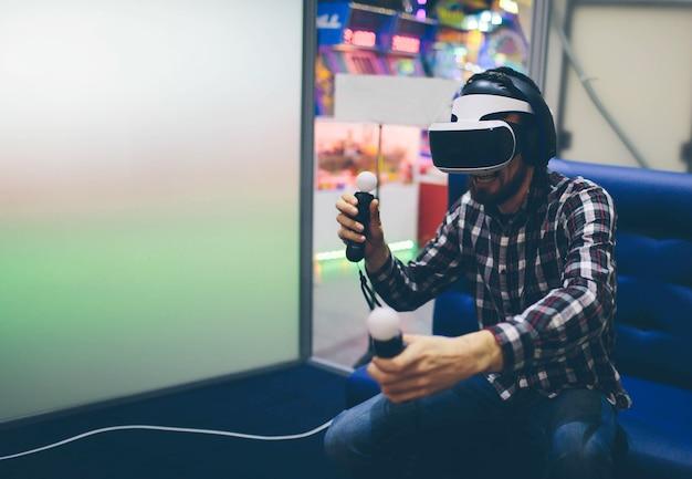 Homem barbudo usando óculos de realidade virtual em coworking moderno smartphone usando com fone de ouvido vr. horizontal, desfocado.