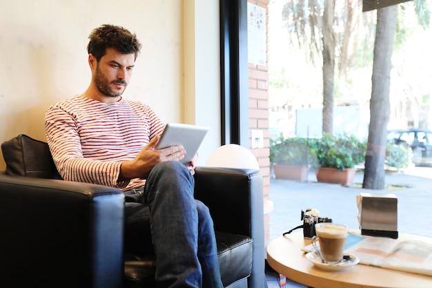 Homem barbudo usando um tablet sentado em um sofá ao lado de uma janela em um café